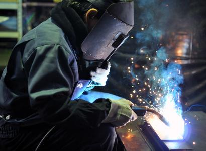 株式会社伊藤鉄工所の男性作業員によるプレス板金部品の溶接作業風景写真