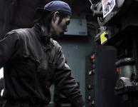 パイプにプレス加工を施す株式会社伊藤鉄工所の男性作業員