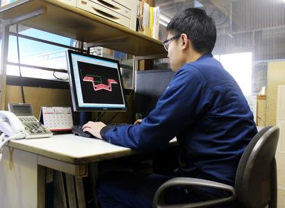 パソコンを使ってプレス板金用のCAD作業をする株式会社伊藤鉄工所の男性